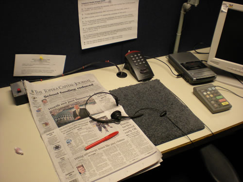 Kansas Audio-Reader studio.  Topeka Capitol-Journal for Thursday, headset and phone dial pad for recording, red pen for marking articles read, cough drop just in case.