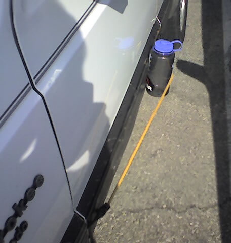 I took this photo of a water bottle strapped with a bungee cord to the outside of a car door.  Any ideas?