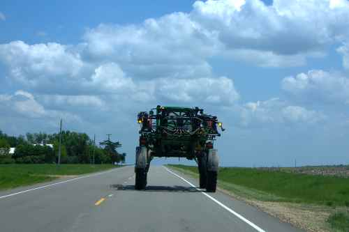 I followed this farm implement on the Farmers' Turnpike yesterday.  Notice how polite the driver is.  He was driving extremely slowly, too.  So, I was able to grab my camera and shoot this through the windshield of my CRV.  ?There was no other traffic, so I felt bold.  Another knock-out Kansas sky as a bonus.