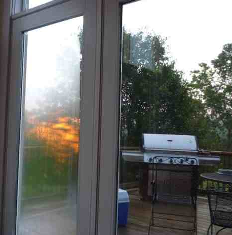 As I was writing at the kitchen table early this morning, I looked up and thought the deck was on fire.  It was the sun rising through the trees.  The glass on the door was wet and skewed the view.  I grabbed my camera and got this. It looks like the grill is shooting flames, sort of.