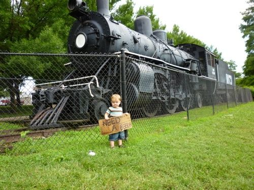 This young man's great grandpa engineered this train during WWII. A hot, dirty job is how he described it.  We found this abandoned sign in the park and the young boy was kind enough to pose for us.