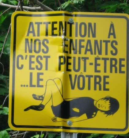 "My niece Helen took this on vacation in Quebec. It translates as ""Watch out for our children. This one could be yours.""  I especially like the sock and missing shoe."