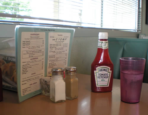 """I love this place.  Single cheeseburger (thin, cheap) with grilled onions, fifty-fifty (half onion rings, half fries), medium limeade. Old waitresses who call you """"Hon."""" Redecorated in the 80's in seafoam green and teal. Yum."""