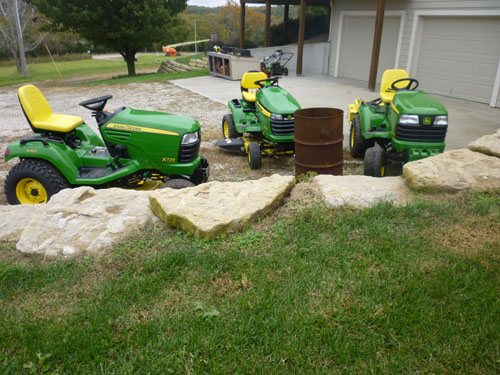 There are now three John Deere machines parked in our driveway.  When the delivery was complete, I went out to inspect and drool.  They were parked around our oil drum, otherwise known as Depression Era firepit. I ran inside to get my camera because I thought they should be documented. So much came to my mind about this scene and its social implications that I am writing about it.