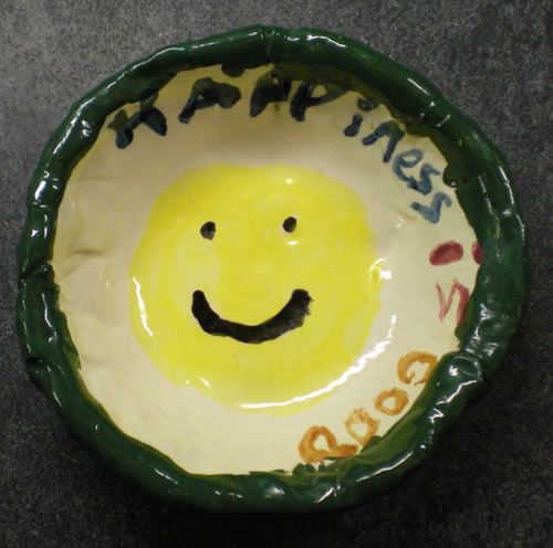 "Handmade clay bowl with happy face and ""happiness is good"" around the rim."