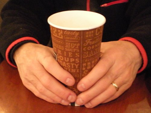 hands holding paper cup