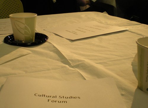 "coffe cups on table at conference.  Pamphlet on table titled ""Cultural Studies Forum""."