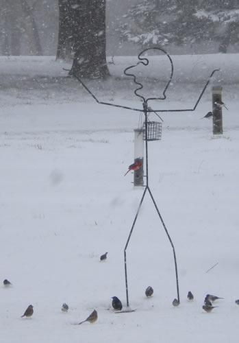 Man-shaped birdfeeder in the snow.