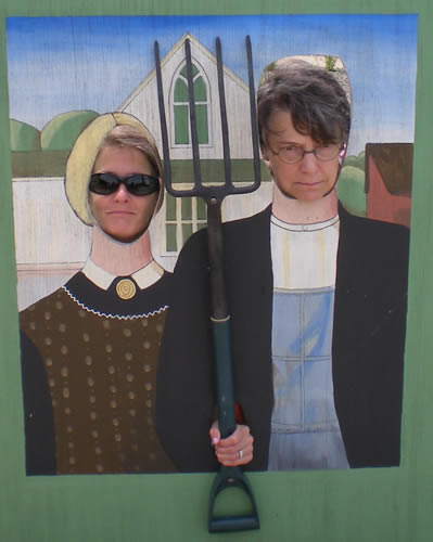 Two women (one in sunglasses) sticking their faces through a fake American Gothic painting