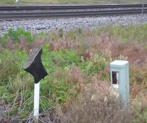 rubber boot upside down on a post beside the railroad tracks