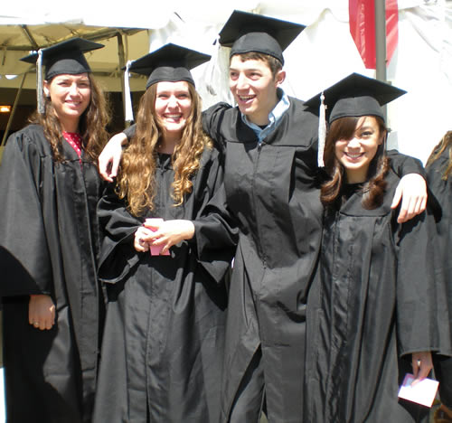 four college graduates in cap & gown