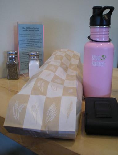 water bottle, salt & pepper, French bread in a bag, menu card