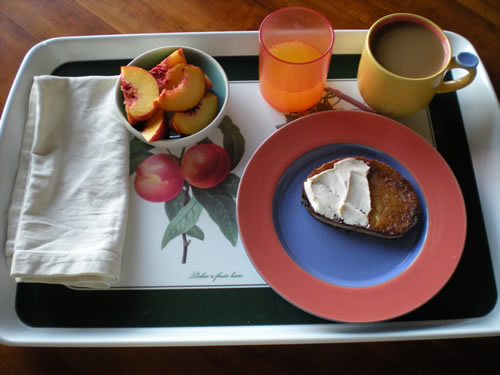 Breakfast tray, cut peach, orange juice, toast, coffee