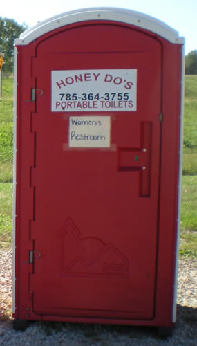 "Red porta-potty with ""Honey-Do's"" sign on front, and hand-lettered sign ""Women's restroom"""