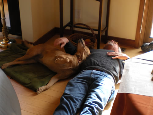 dog and man lying on the floor.