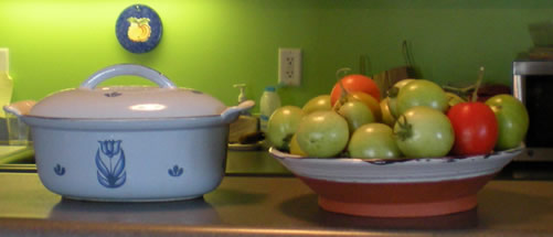 casserole dish, green wall behind, dish of red and green tomatoes.